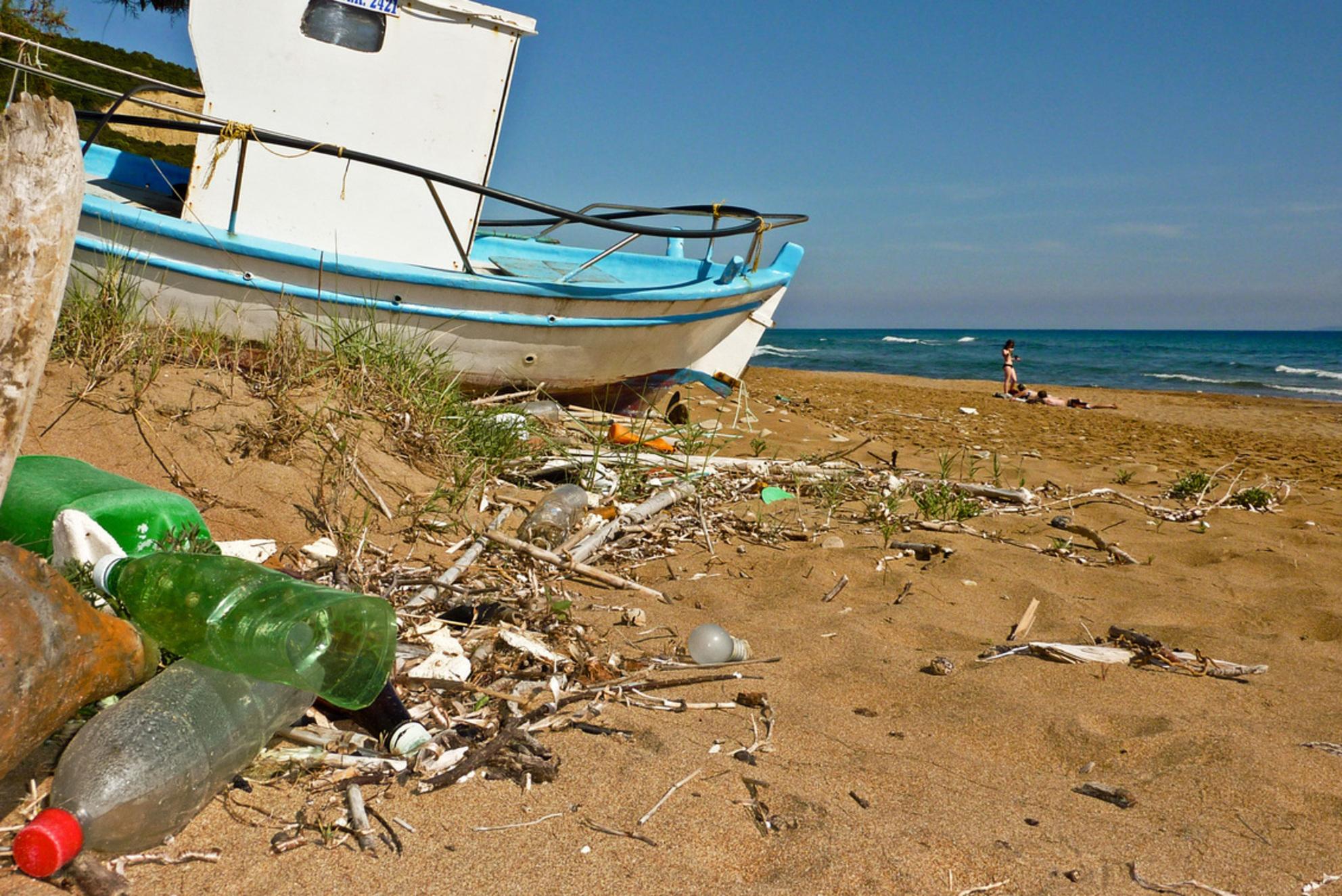 Mediterraan Vergezicht - Mediterraan strand met plastic flessen een verlaten vissersboot en in de verte een paar zonnende badgasten. - foto door marcl op 09-05-2010 - deze foto bevat: zon, strand, zee, bootje, mediterraan - Deze foto mag gebruikt worden in een Zoom.nl publicatie