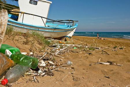 Mediterraan Vergezicht - Mediterraan strand met plastic flessen een verlaten vissersboot en in de verte een paar zonnende badgasten. - foto door marcl op 09-05-2010 - deze foto bevat: zon, strand, zee, bootje, mediterraan