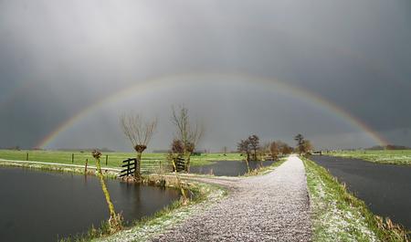 Maartse bui - een maartse hagelbui gevolgd door de zon maakt een mooie regenboog boven de witte polderweg. groeten, Bert - foto door b.neeleman op 20-03-2016 - deze foto bevat: lucht, zon, lente, regenboog, polder, hagelbui