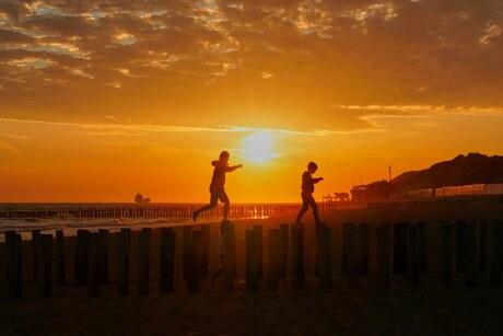 Zonsondergang met kids op de golfbreker