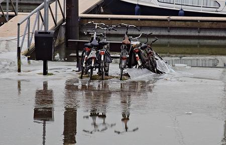 Wachten op de baas - Deze fietsen hebben hoog water meegemaakt. Tot aan zadel. Kunnen straks wel een beetje vet en olie gebruiken ! - foto door huubwest op 16-02-2021 - deze foto bevat: water, dijk, boot, sneeuw, winter, ijs, landschap, haven, rivier, polder