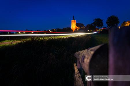 Uiterwaarden van de IJssel - Tussen Kampen & Zwolle ligt dit slaperig dorpje (Wilsum) met een van de oudste kerken uit de regio die het rivier landschap domineert. Voeg een rondr - foto door Fotografiecor op 27-12-2020 - deze foto bevat: lucht, hek, dijk, natuur, licht, avond, zonsondergang, landschap, auto, tegenlicht, bomen, kerk, maan, rivier, nacht, polder, verkeer, contrast, weiland, overijssel, groothoek, lichtstrepen, lightpainting, blauwe uur, lange sluitertijd, long exposure