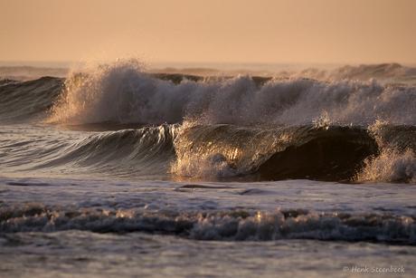 Laatste zonnestralen strijken over golven
