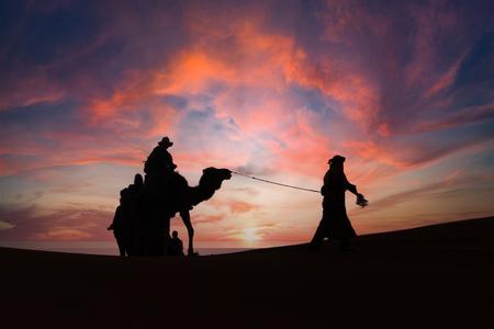Walking in the desert - Het is altijd een feestje om een karavaan te zien in de woestijn. - foto door anitagrotewal op 10-04-2021 - locatie: Erg Chebbi, Marokko - deze foto bevat: wolk, lucht, ecoregio, gebaar, mensen in de natuur, nagloeien, natuurlijk landschap, rode lucht 's ochtends, landschap, horizon