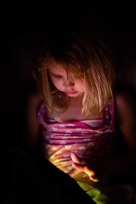 iPad licht - Isa in het licht van de iPad - foto door DanielleSchimmelFotografie op 12-12-2018 - deze foto bevat: donker, portret, schaduw, kind, nikon, meisje, blond, 35mm