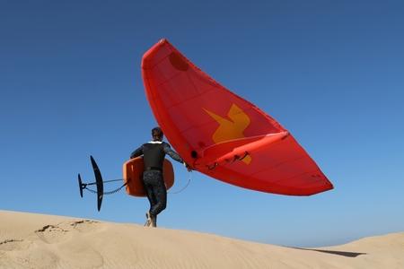 rood - kitesurfen  - foto door onne1954 op 09-04-2021 - deze foto bevat: rood, surfen, kitesurfen, duinen, zand, lucht, sportuitrusting, vliegreizen, mensen in de natuur, windsport, vleugel, helling, wind, reizen, sport