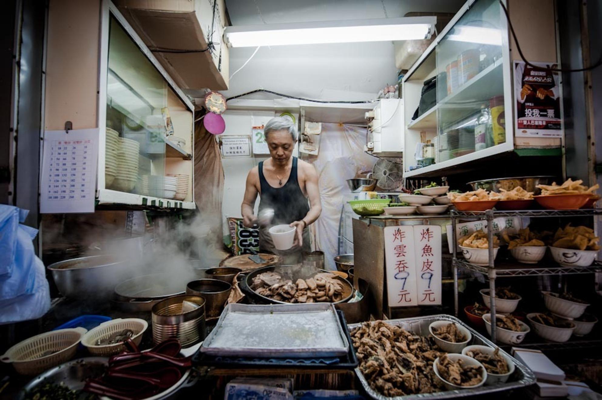 Kijkje in de keuken - Na een paar uur rondslenteren door Hong Kong kwam ik in een van de vele straatjes die deze stad rijk is dit mobiele eettentje tegen. Met wat wijzen s - foto door voss op 13-07-2012 - deze foto bevat: man, eten, portret, markt, food, keuken, china, straatbeeld, chinees, hongkong, hong kong, streetfood - Deze foto mag gebruikt worden in een Zoom.nl publicatie