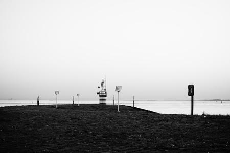 Pier - Hansweert - Zicht op een pier vanaf de Verkeerspost/Radartoren te Hansweert, Zeeland. - foto door Krulkoos op 18-05-2018 - deze foto bevat: zee, water, dijk, avond, stilleven, eenzaam, zicht, pier, zeeland, holland, zwartwit, wandelen, transport, eenzaamheid, stil, alleen, radar, balans, maritiem, schelde, wandelaar, hansweert, verkeerspost, radartoren, zwartwitfotografie, maurice weststrate