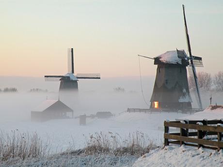 molen in de mist bij sneeuw, zonlicht in raam
