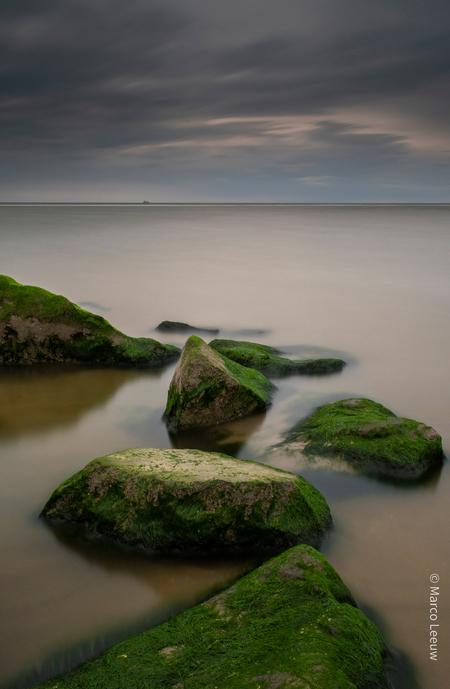 Katwijk strand - Lange sluitertijd strand. Was redelijk donker aan het worden. Liggen mooie stenen bij de uitwatering in Katwijk - foto door mcgleeuw op 26-07-2020 - deze foto bevat: lucht, wolken, zon, strand, zee, water, panorama, natuur, licht, avond, zonsondergang, landschap, duinen, zand, nacht, kust, katwijk, mysterieus, lange sluitertijd
