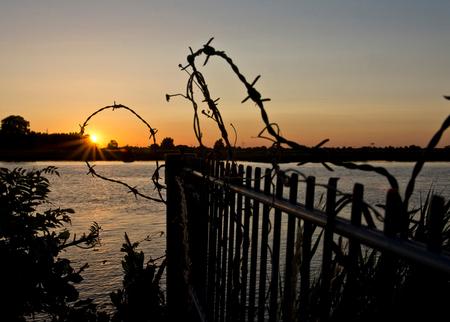 Doorkijkje - Ondergaande zon in een ring van prikkeldraad. - foto door Koningsbruggen op 06-08-2019 - deze foto bevat: ondergaande zon, ijssel ondergaande zon