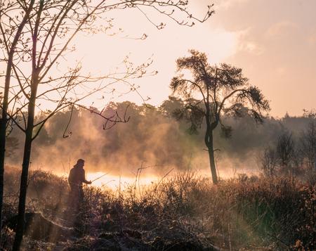 """Oisterwijkse ven - Lucky shot met deze """"visser"""". Is dus een collega fotograaf die zijn statief indraaide. Maar ik zag gelijk het beeld van een visser voor mij en schoot - foto door Olga-schraven op 13-04-2021 - deze foto bevat: oisterwijk, mist, ochtendzon, ven, landchapsfotografie, flair, fabriek, atmosfeer, lucht, plant gemeenschap, ecoregio, wolk, natuurlijk landschap, mensen in de natuur, afdeling, boom"""