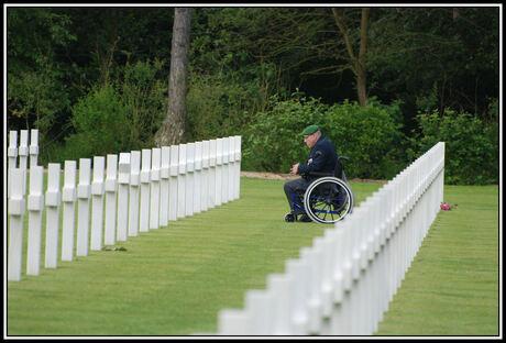 Een oorlogsveteraan rouwt bij het graf van zijn overleden kameraad.