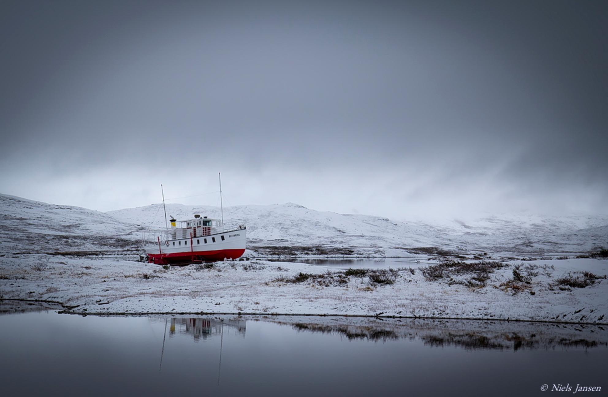 Boot op het droge - Tijdens een autorit door het fantastisch mooie natuurgebied Jotunheimen lag daar ineens een boot...  Bedankt voor jullie reacties op 'Staafkerk van - foto door NielsJansen op 24-10-2014 - deze foto bevat: lucht, water, boot, sneeuw, spiegeling, landschap, bergen, noorwegen, grijs, jotunheimen, surrealistisch, niels jansen - Deze foto mag gebruikt worden in een Zoom.nl publicatie