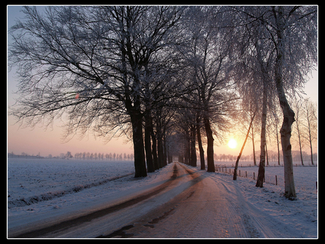 Besneeuwde weg bij zonsondergang