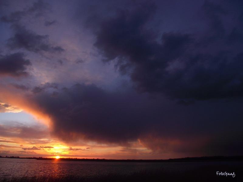 Buitje op komst - Een stukje verder gereden (zie ook mijn twee vorige foto's) met uitzicht over het Lauwersmeergebied en de buien verder gevolgd. Hier ging de zon inmi - foto door vdbergamanda op 31-03-2016 - deze foto bevat: lucht, zon, regen, bui, zonsondergang, dreigend, regenbui