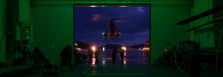 Inkomend voor landing - Helicopter doet een nachtlanding aan boord tijdens een oefening. De lichtkleur in de hangar is zo gekozen dat de piloot geen last heeft van het lich - foto door ruba1000 op 15-03-2012 - deze foto bevat: groen, donker, nacht, schip, landing, helicopter, marine, heli, cougar