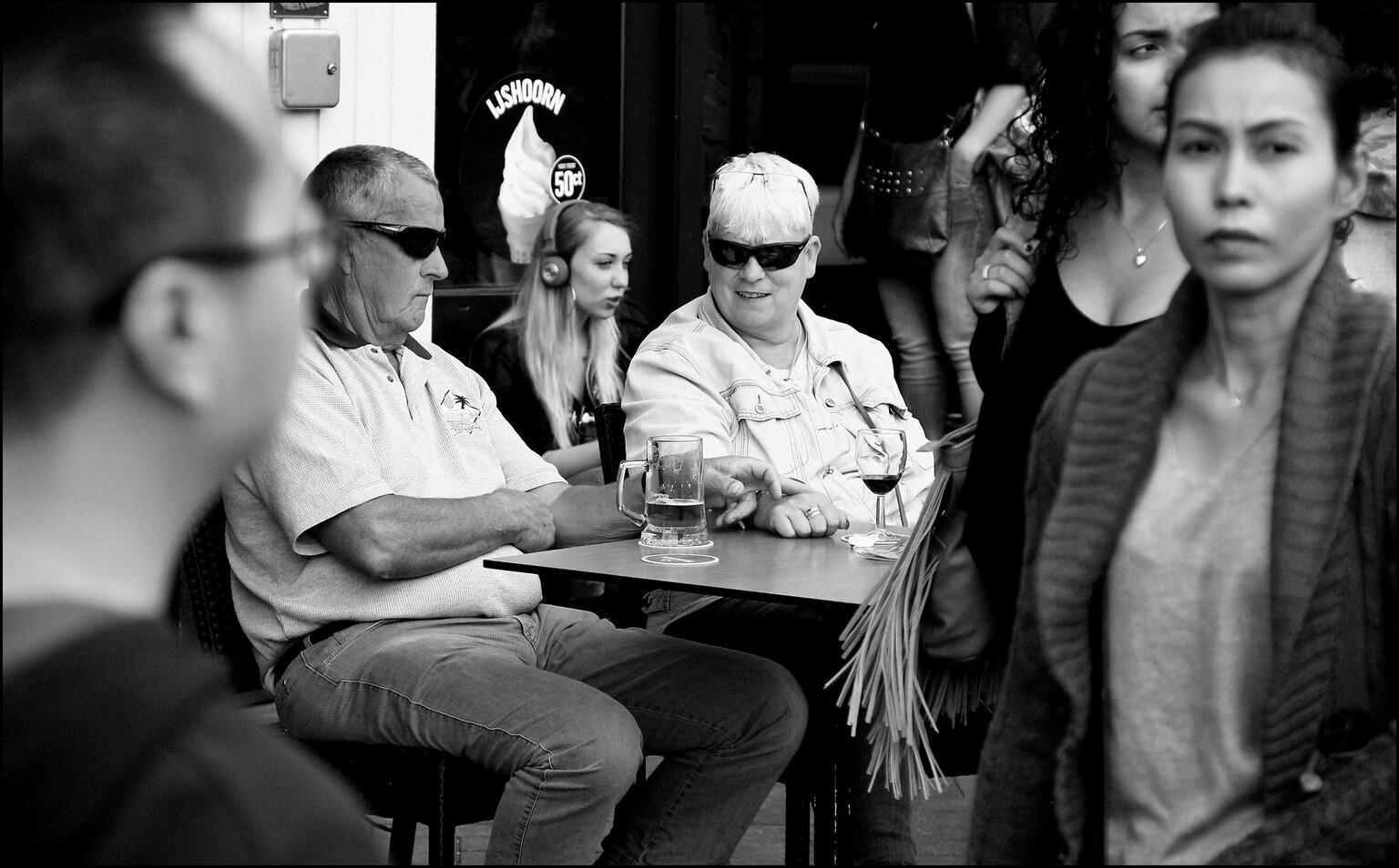 Toenadering - Damrak, Amsterdam 2017  Ik ben blij met alle mooie waarderingen bij mijn vorige foto: Ik zie je wel!! Allen bedankt! Grt Mary - foto door MaryBruijn op 18-04-2021 - locatie: Amsterdam, Nederland - deze foto bevat: mensen, terras, zwartwit, straatfotografie, kleding, zwart, brillen, staand, zwart en wit, tafel, oogzorg, stoel, stijl, interactie