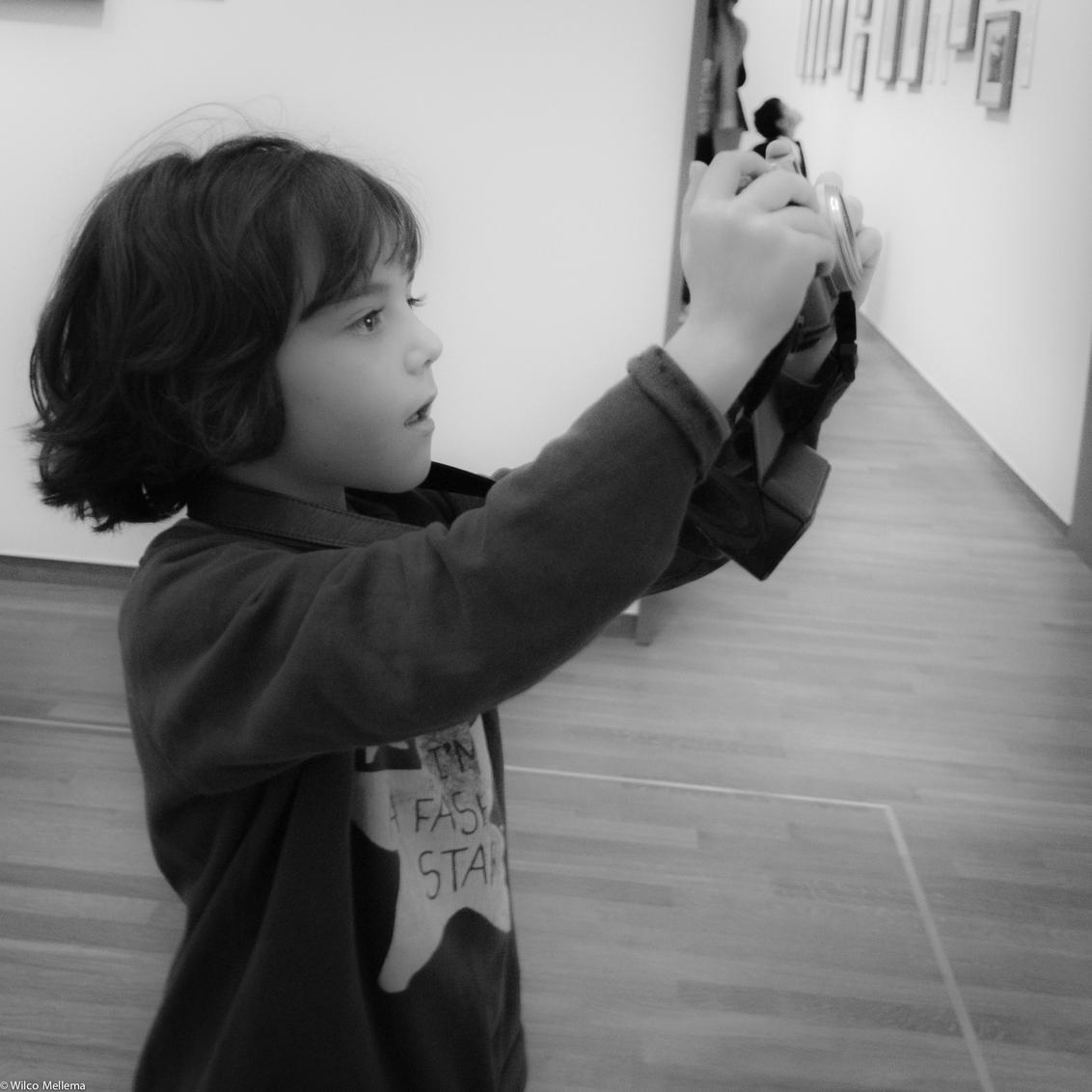 Foto van een foto - Een klein meisje is tijdens een tentoonstelling in het Rijksmuseum druk bezig om alle getoonde werken (van een fototentoonstelling) zelf op de foto t - foto door wilcofm op 30-05-2015 - deze foto bevat: mensen, kind, kinderen, meisje, zwartwit