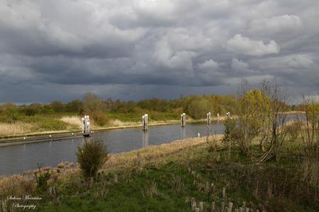Dreigende luchten - Dreigende luchten maar achter mij scheen de zon  - foto door sabinameermanphotography op 15-04-2021 - locatie: 4655 De Heen, Nederland - deze foto bevat: de heen, dreigende luchten, wolken, natuur, water, zon, brabant, canon, wolk, water, fabriek, lucht, natuurlijk landschap, meer, bank, cumulus, boom, gewoon