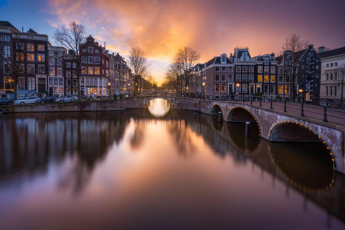 Amsterdam - Een prachtige zonsondergang in Amsterdam afgelopen weekend. - foto door EllenD op 14-01-2021 - deze foto bevat: lucht, amsterdam, water, licht, avond, zonsondergang, spiegeling, landschap, tegenlicht, brug, grachten, lange sluitertijd