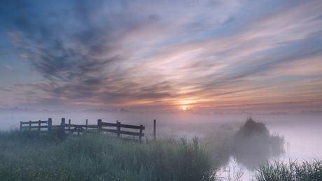 Zonsopkomst boven een mistig polderlandschap