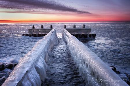 IJsselmeer Afsluitdijk - Bevroren IJsselmeer, met ijs bedekte  steiger aan Afsluitdijk ter hoogte van het monument. - foto door josreimering op 18-02-2021 - deze foto bevat: wolken, zon, zee, natuur, sneeuw, winter, ijs, landschap, tegenlicht, zonsopkomst, monument, meer, kust, ijsselmeer, afsluitdijk, lange sluitertijd