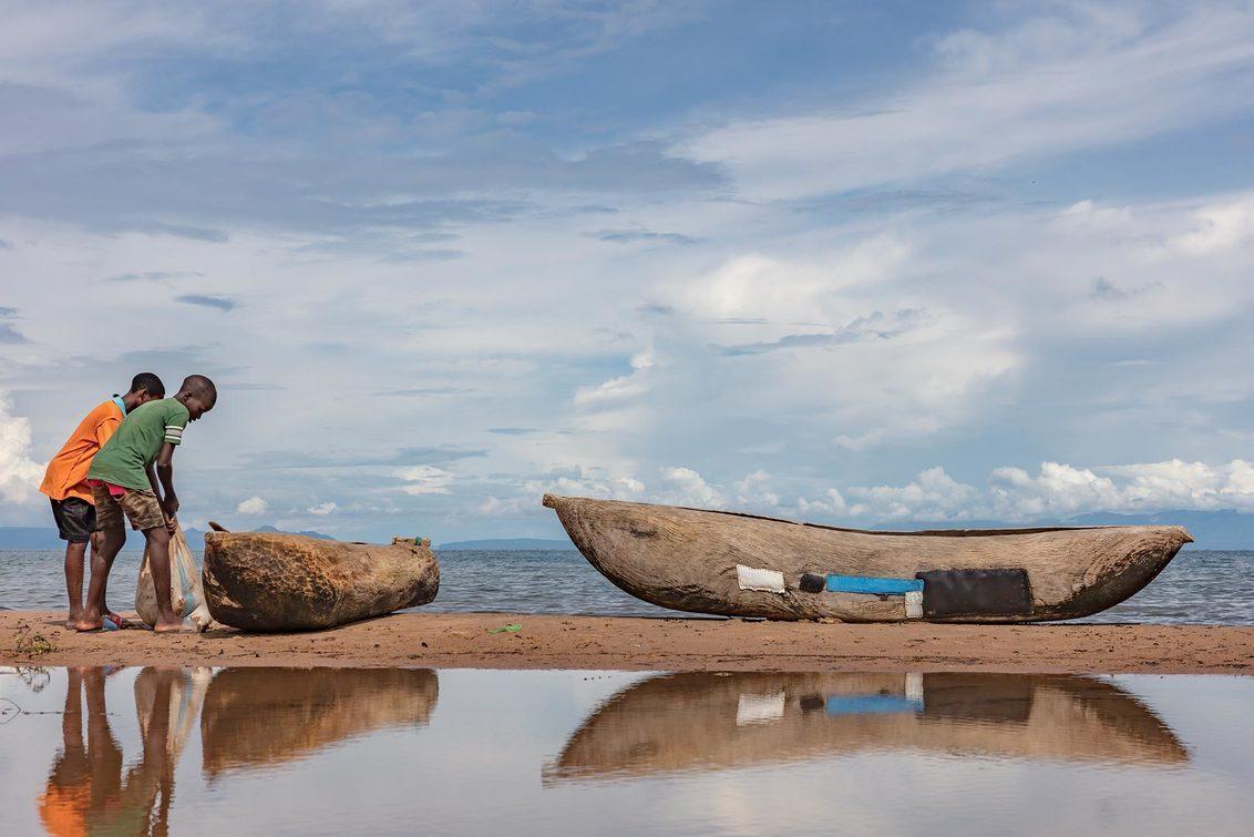 Boys preparing for fishing. - 2 jongens die hun boot aan het klaarmaken zijn om te gaan vissen. - foto door EdPeetersPhotography op 04-01-2021 - deze foto bevat: wolken, uitzicht, strand, water, natuur, reizen, landschap, meer, afrika, straatfotografie, reisfotografie, malawi, edpeetersphotography, chitimba