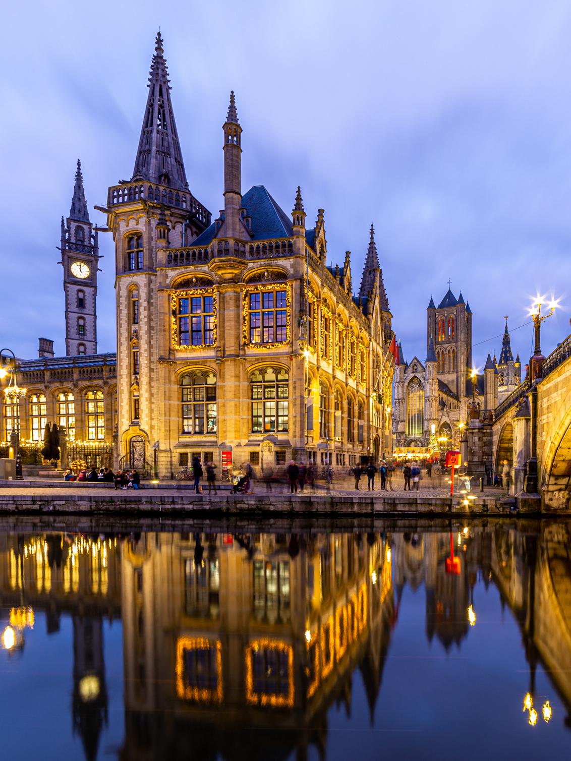 Kerst in Gent - Gent een bekende mooie stad in Belgie. In december tref je een mooie verlichte stad en een gezellige kerstmarkt - foto door lbfoot op 22-12-2019 - deze foto bevat: water, spiegeling, landschap, kerk, brug, belgie, gent, verlichting, leie, toerisme, postkantoor, europa, twilight, blue hour