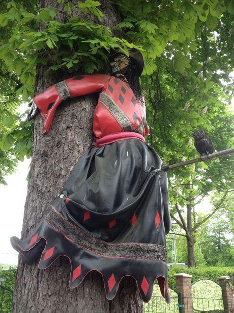 Heks vliegt tegen boom