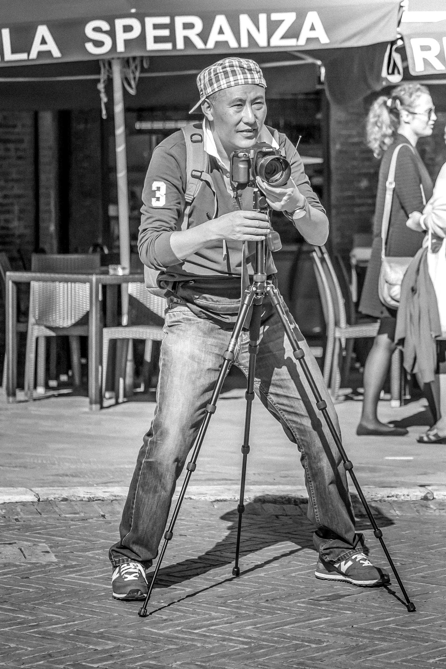 De fotograaf - Piazza del Campo, Siena - foto door RobMenting op 16-04-2021 - locatie: Il Campo, 53100 Siena SI, Italië - deze foto bevat: broek, statief, wit, camera, staand, zwart en wit, stijl, videograaf, musicus, camera's en optica