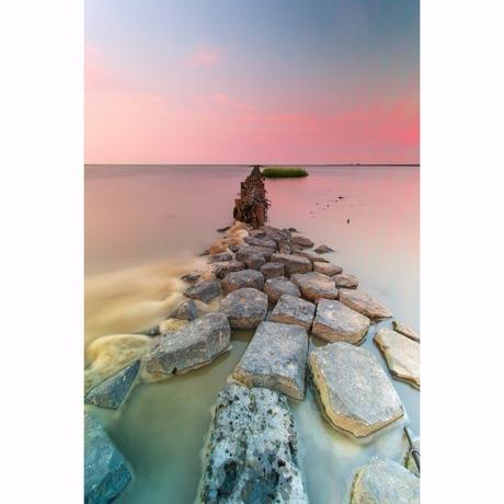 Zonsondergang achter de dijk bij Lauwersoog
