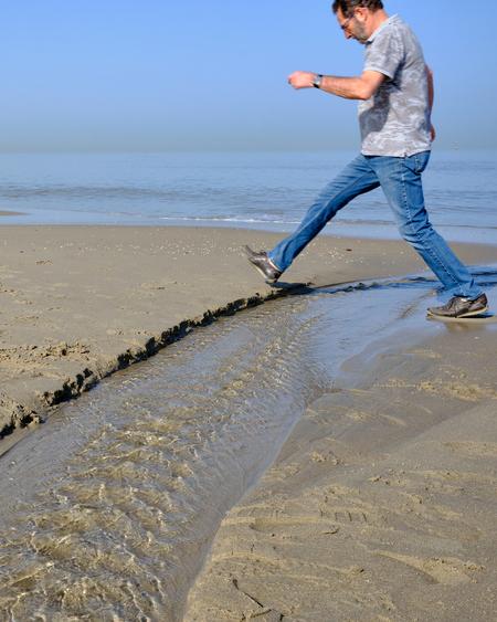 Een reuzenstap - Omgeving Loosduinen - foto door Eugenio op 11-04-2021 - deze foto bevat: duinen, strand, zee, branding, water, water, lucht, wolk, been, mensen in de natuur, azuur, flitsfotografie, strand, mensen op het strand, staand