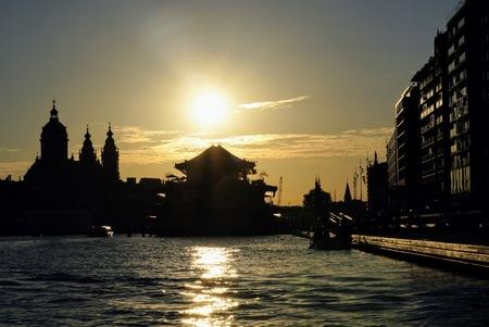 Amsterdam zonsondergang - Zomer vanaf de rondvaartboot - foto door Frenk2021 op 11-04-2021 - locatie: Amsterdam Centraal, Stationsplein, 1012 AB Amsterdam, Nederland - deze foto bevat: water, lucht, wolk, gebouw, dag, wereld, nagloeien, verlichting, zonlicht, schemer