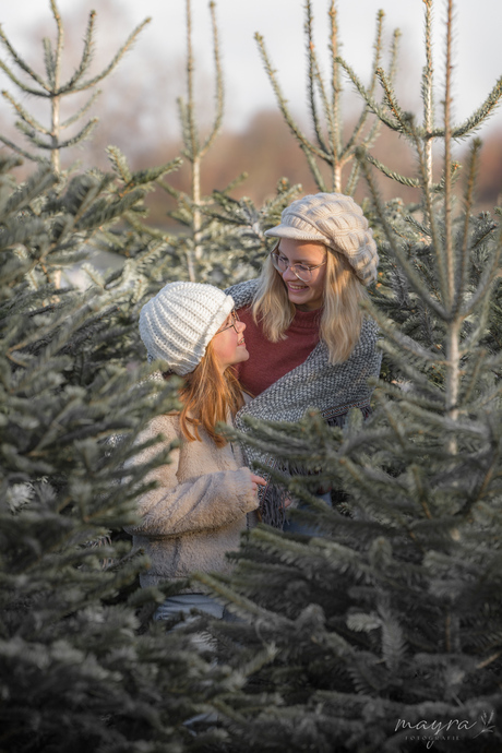 Zusjes tussen winterse kerstbomen