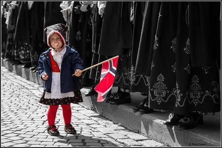 Met Vlag En Speen - Een oudere foto die ik opnieuw bewerkt heb. Deze is genomen tijdens de jaarlijkse viering van de onafhankelijkheid op 17 mei in Ålesund.   Alsnog b - foto door NielsJansen op 30-06-2015 - deze foto bevat: mensen, kleur, straat, vlag, meisje, noorwegen, bewerking, zwartwit, feest, straatfotografie, traditie, kleding, speen, nationale feestdag, niels jansen, traditionele kleding, 17 mei, aalesund, onafhankelijksdag, zwarte schoenen, bunad
