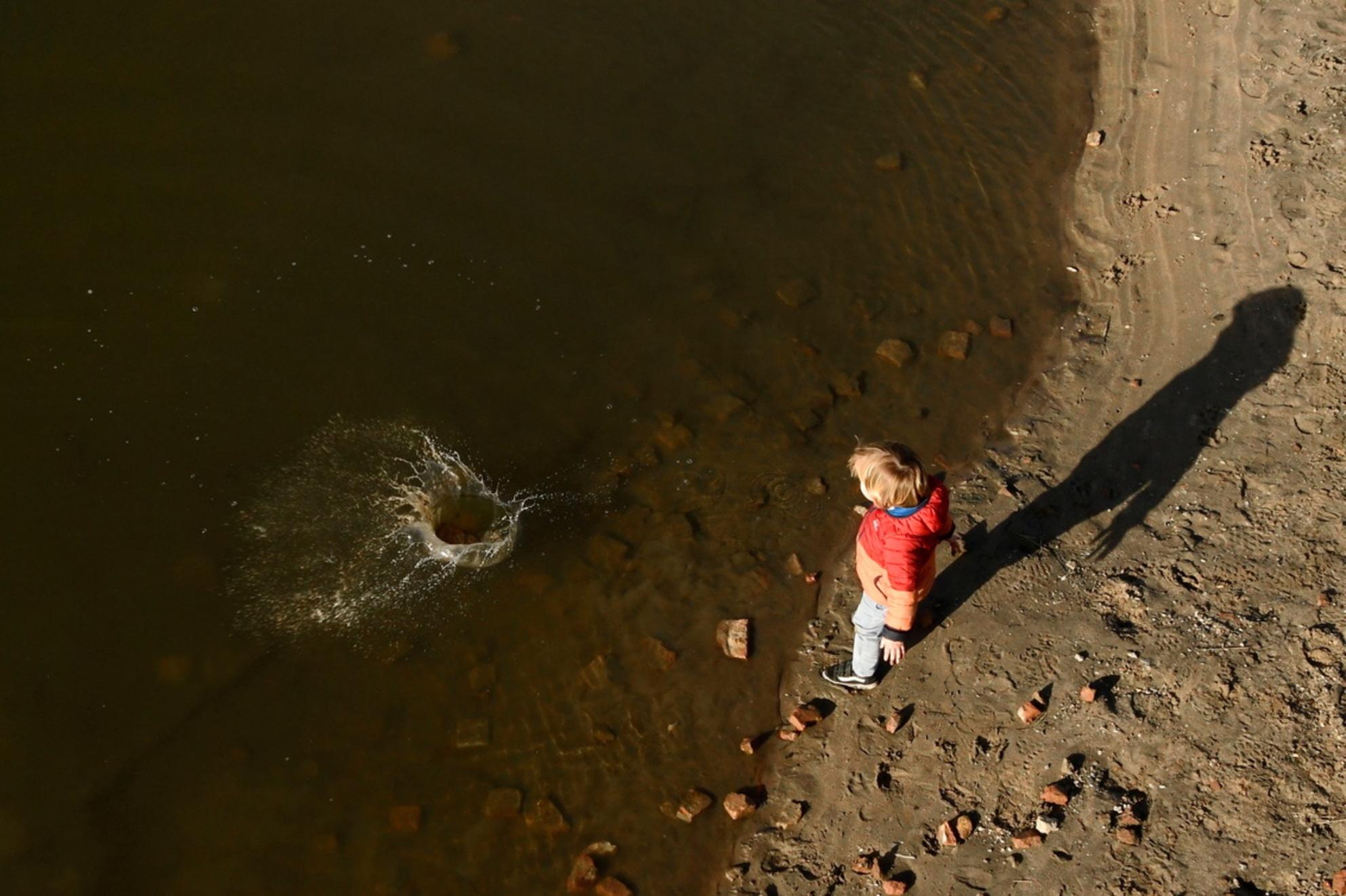 Stenen gooien in het water - Naar het uitkijkpunt bij Fort Blauwesluis om vogels te spotten, maar met zoveel plezier gekeken naar een vader met zijn zoontje, die eindeloos stenen - foto door Dieke Steeg op 28-02-2021 - deze foto bevat: mensen, rood, kleur, water, druppel, licht, kind, jongen, maas, stenen, beweging