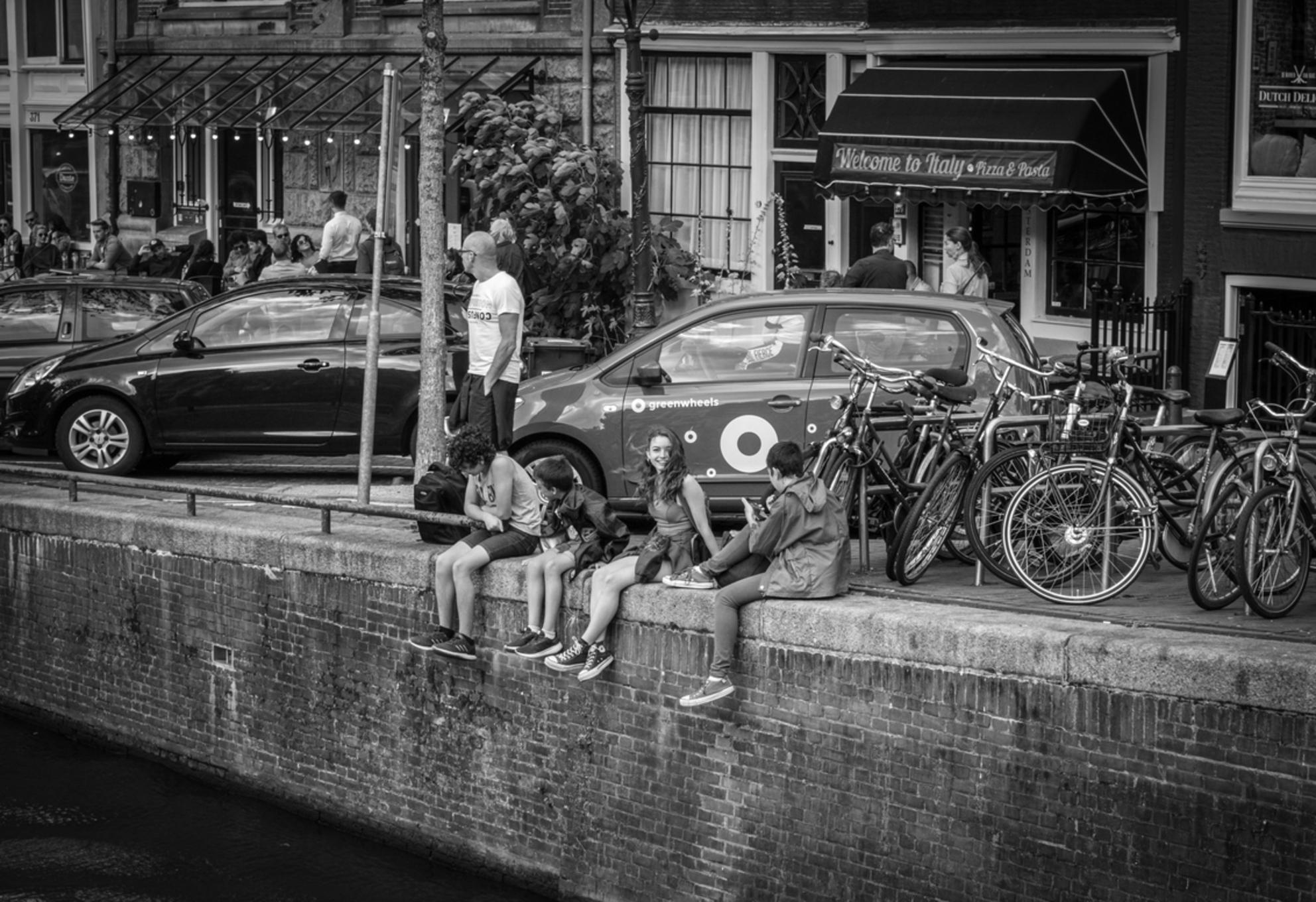 Kinderen chillen aan de gracht in Amsterdam - Kinderen zijn aan het relaxen aan de Amsterdamse grachten - foto door Bamvlier op 24-10-2020 - deze foto bevat: man, mensen, amsterdam, stad, kinderen, meisje, zwartwit, straatfotografie, grachten, relaxen - Deze foto mag gebruikt worden in een Zoom.nl publicatie