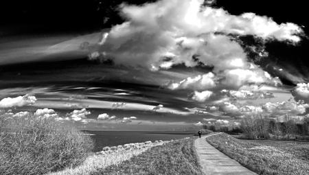 donker - Wandel en fietspad langs het IJmeer over de natuurboulevard. Wederom een omzetting naar zwart wit via roodfilter en aanpassingen.   gr hans - foto door sparks_zoom op 31-03-2020 - deze foto bevat: wolken, donker, dijk, muiden, wandelaar, sparks