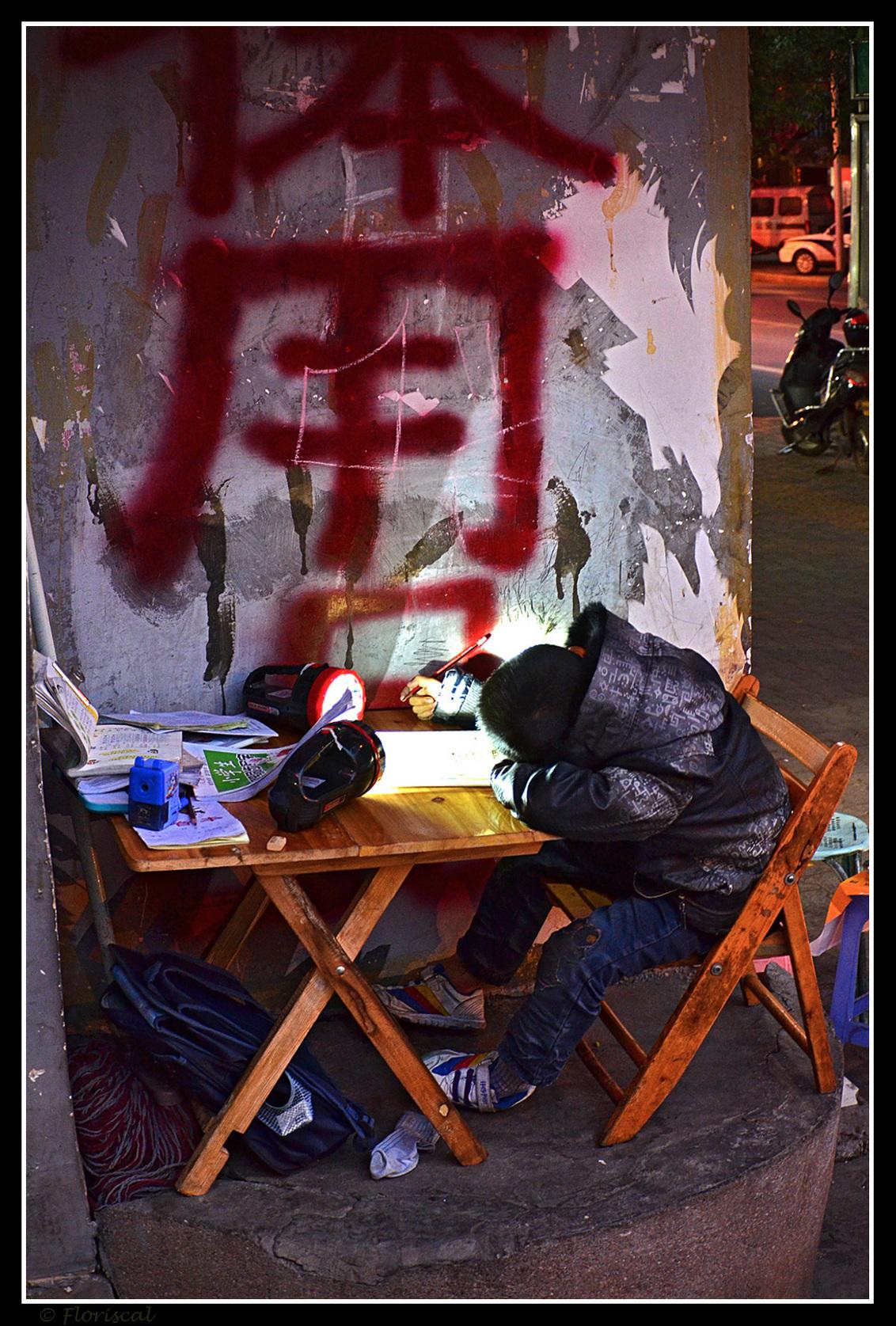 Studie - Huiswerk maken. Het is zo vanzelfsprekend, op je kamer met een muziekje erbij. Maar hier in China gaat dit niet altijd op. Hier op de hoek van de str - foto door Floriscal op 10-06-2015 - deze foto bevat: straat, avond, stad, kind, china, straatfotografie