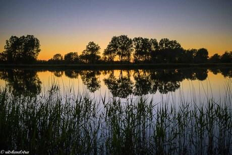 Ondergaande zon spiegelt in het Maalwater.