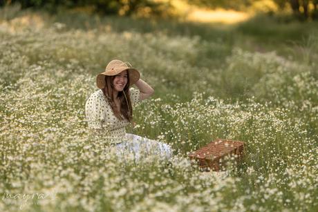 Zomers portret van jonge vrouw met strohoedje in wilde bloemen veldje tijdens het gouden uurtje