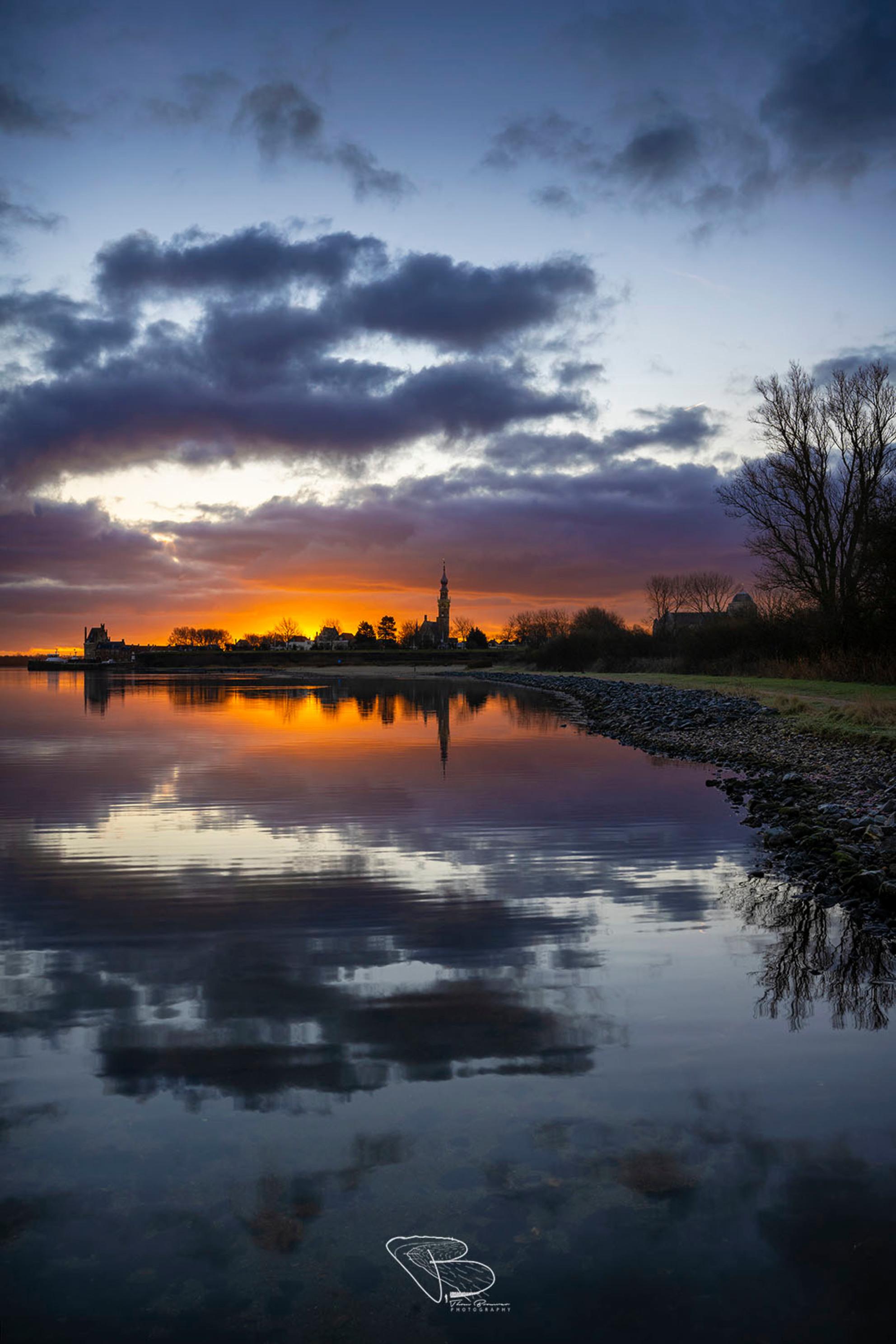 Veere Skyline - Een imposante lucht tijdens zonsopkomst aan het Veerse Meer, waar de skyline van Veere zichtbaar is. - foto door Thombrouwer op 11-01-2021 - deze foto bevat: lucht, wolken, winter, spiegeling, landschap, zonsopkomst, meer, skyline, zeeland, kust, weerspiegeling, veere, Veerse meer