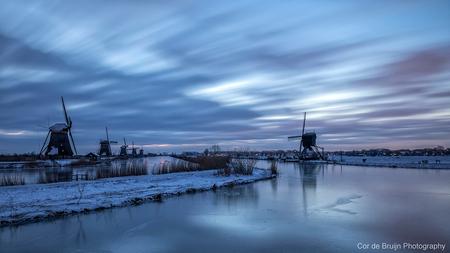 Kinderdijk - De molens van Kinderdijk voor zonsopkomst met sneeuw en ijs in de koude periode van februari 2021. - foto door CordeBruijn op 26-02-2021 - deze foto bevat: lucht, wolken, water, licht, sneeuw, winter, landschap, zonsopkomst, molen, polder, lange sluitertijd