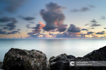 Overdrijvende wolken - Mooie avonden langs de oevers van het IJsselmeer. - foto door Fotografiecor op 07-03-2021 - deze foto bevat: lucht, wolken, zon, zee, water, dijk, panorama, natuur, licht, avond, waterkant, zonsondergang, spiegeling, landschap, mist, tegenlicht, zonsopkomst, meer, kust, ijsselmeer, stavoren, hdr, groothoek, filters, lange sluitertijd, long exposure