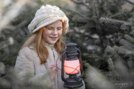 Portret van meisje in de sneeuw met lantaarn