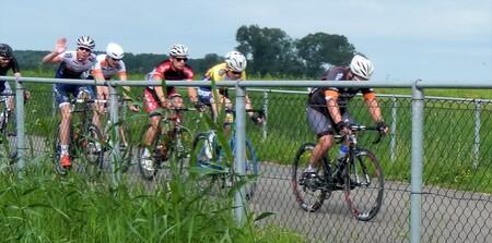 wielrenners - een aantal jaren geleden waren we aan de wandel bij de Nedereindse Plas in Nieuwegein, er is daar ook een wielerbaan waar op dat moment een wedstrijd - foto door Tonny1946 op 17-07-2020 - deze foto bevat: gras, groen, lucht, rood, wit, blauw, geel, zwart, bomen, hekwerk, grijs, wielrennen, wielerbaan, juli 2016, nieuwegein.zomer