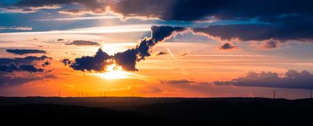 Zonnewind - De zonsondergang op onze laatste avond in Luxemburg. De naam voor de foto 'Zonnewind' heb ik bedacht omdat je natuurlijk de zon ziet, maar ook windmo - foto door Sake-van-Pelt op 20-04-2017 - deze foto bevat: lucht, wolken, zon, panorama, lente, natuur, groene, klein, licht, avond, wind, zonsondergang, vakantie, landschap, schaduw, silhouette, tegenlicht, bomen, bergen, windmolen, molens, zwitserland, luxemburg, schaduwen, windkracht, horizon, energie, lagen, beaufort, groene energie, Klein Zwitserland