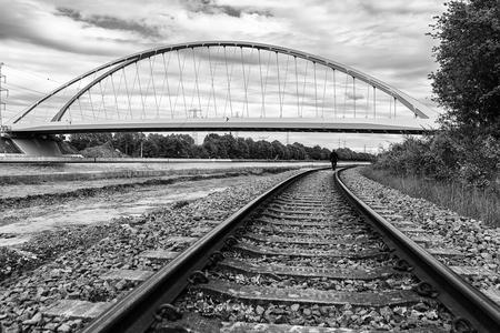brug - brug met spoorweg en wandelaar - foto door gerboon op 08-04-2021 - locatie: 2440 Geel, België - deze foto bevat: lucht, wolk, fabriek, infrastructuur, boom, gebonden boogbrug, track, zwart en wit, stijl, doorgaande weg