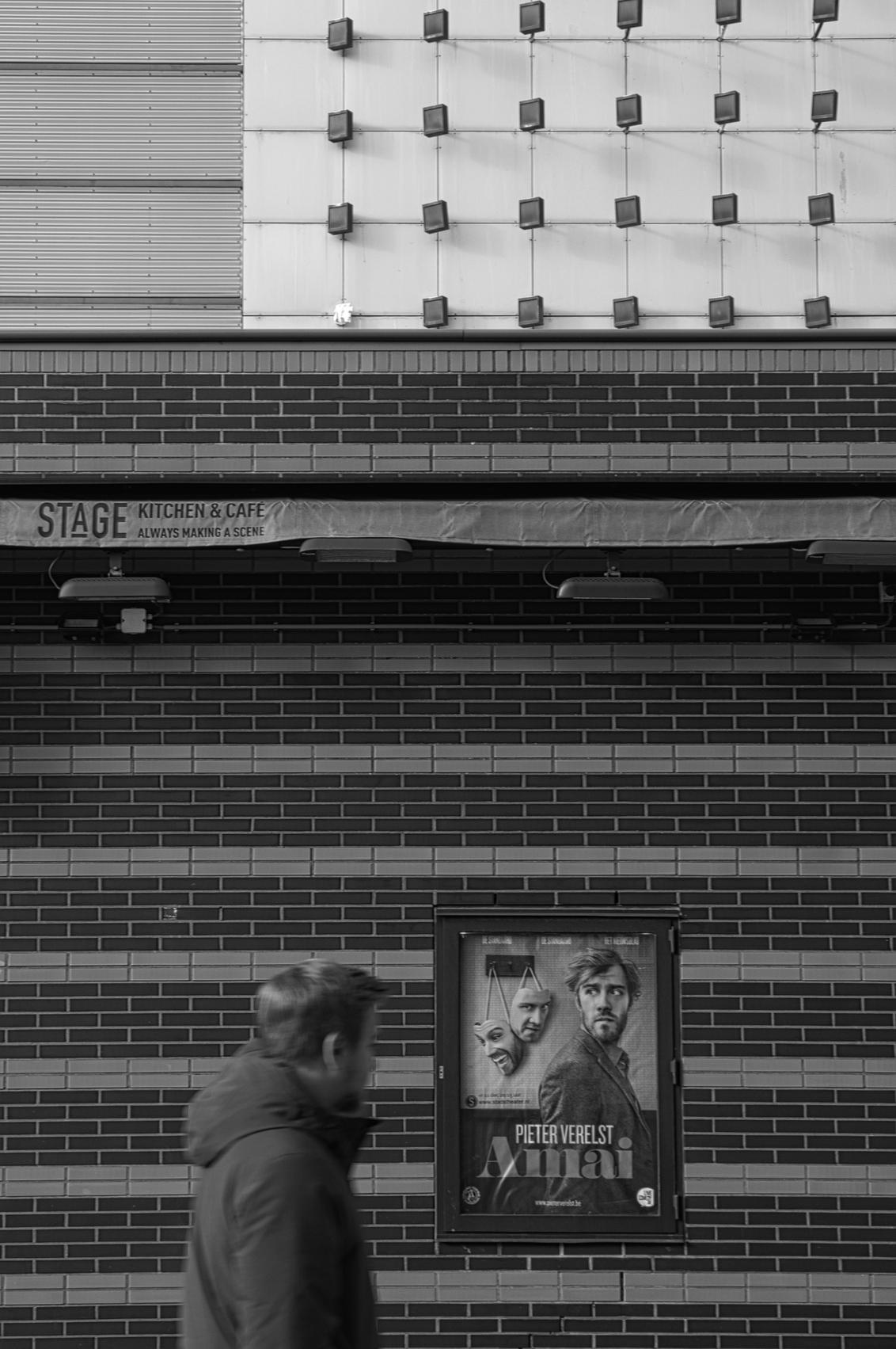 Kijk - Wie kijkt naar wie.   Alle zoomers, zoomvrienden en -volgers, bedankt voor de waardering, tips en aandachtspunten op mijn vorige upload - foto door PaulvanVliet op 07-03-2021 - deze foto bevat: cafe, man, poster, mensen, straat, licht, portret, architectuur, stad, theater, zwartwit, beweging, straatfotografie, centrum, zoetermeer, baard, stadshart, wandelaar, affiche, stadstheater, cadenza